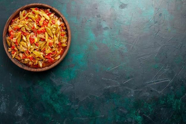 紺色の背景にさまざまな材料で調理された上面図スライス野菜ミール