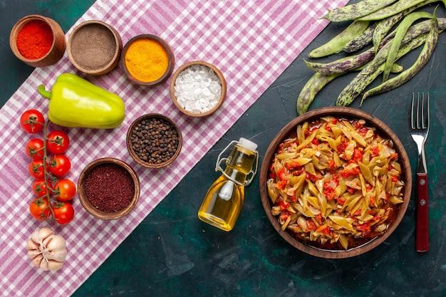 上面図スライスした野菜の食事青い背景にさまざまな調味料とおいしい豆の食事