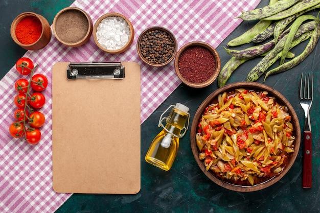 파란색 책상에 다른 조미료와 상위 뷰 슬라이스 야채 식사 맛있는 콩 식사