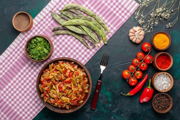 青い机の上にさまざまな調味料を使った上面スライス野菜料理おいしい豆料理