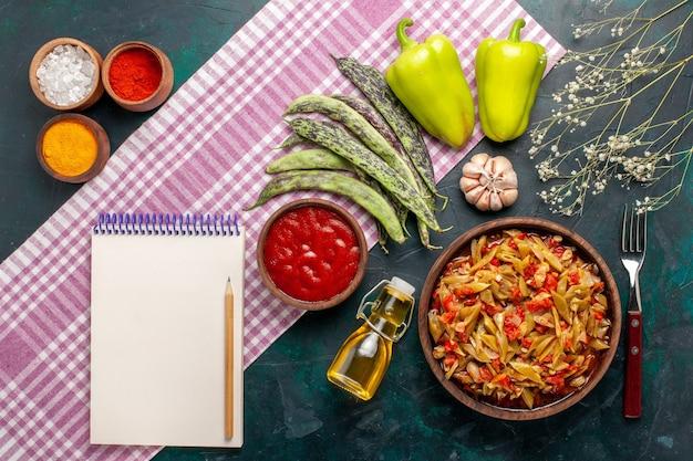 上面図スライスした野菜の食事オリーブオイルと青い机の上の調味料とおいしい豆の食事