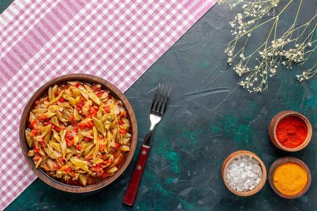 상위 뷰는 파란색 배경에 갈색 냄비 안에 콩 야채 식사 맛있는 식사를 슬라이스