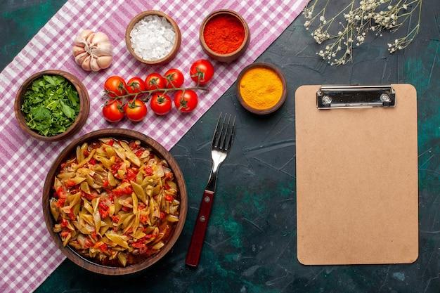Вид сверху нарезанной овощной еды, вкусной еды с фасолью в коричневом горшке на синем фоне