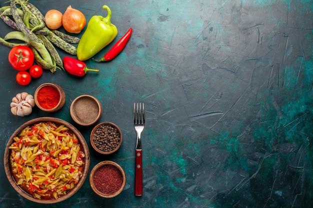 紺色の背景にさまざまな材料と調味料を使った上面スライス野菜ミール