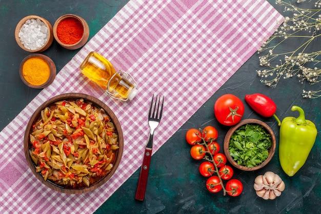 紺色の背景にさまざまな調味料でスライスした野菜の食事の上面図