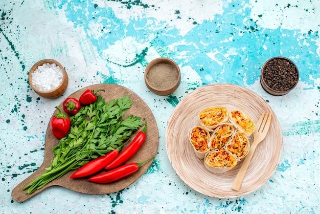 上面図スライスした野菜は、明るい青色の机の上に緑と赤のスパイシーな唐辛子と一緒においしいフィリングで生地をロールします食品写真カラーロール野菜