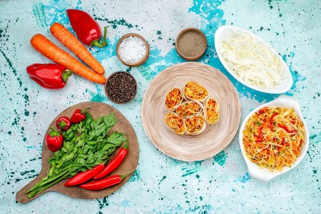 Vista dall'alto di involtini di verdure a fette impasto con gustoso ripieno insieme a insalata di carote verdi e peperoni piccanti rossi sullo spuntino del pasto del rotolo di colore alimentare della scrivania blu brillante