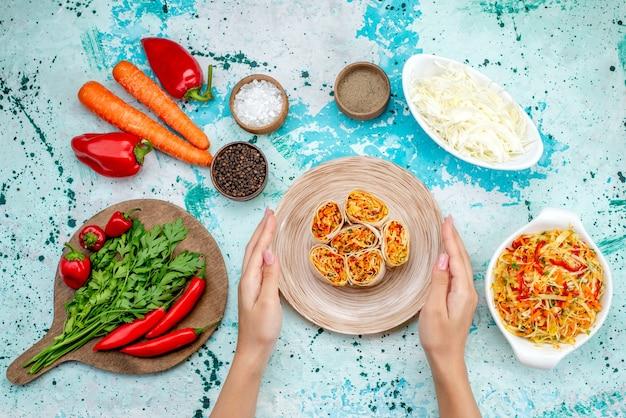Vista dall'alto involtini di verdure a fette impasto con gustoso ripieno insieme a insalata di carote verdi e peperoni rossi piccanti sulla scrivania blu brillante rotolo pasto spuntino verdura