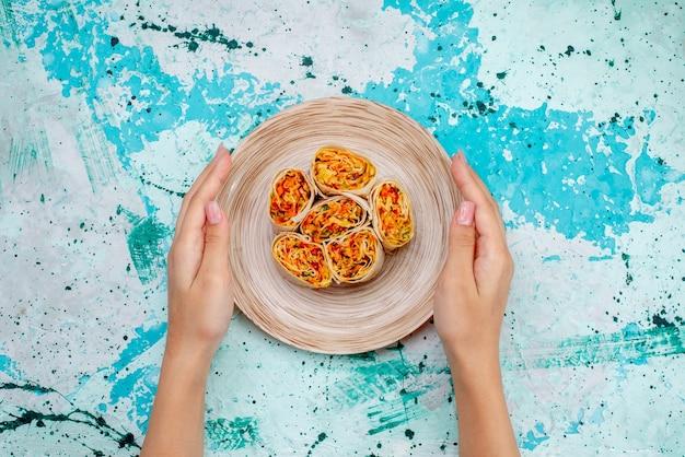 上面図スライスした野菜ロール生地、明るい青色の机の上に女性が保持するおいしいフィリング食品着色料ロールミールスナック
