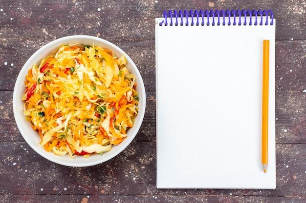 Vista dall'alto insalata di verdure affettata fresca e salata all'interno della piastra con il blocco note sulla foto fresca di piatto di cibo vegetale pasto piatto di legno rustico marrone scrivania