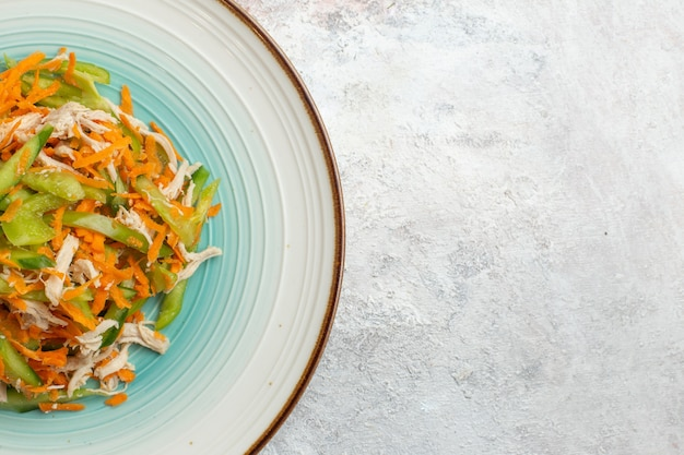 Vista dall'alto di insalata di verdure a fette all'interno della piastra su sfondo bianco chiaro