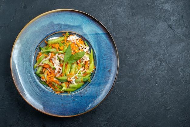 어두운 회색 배경에 접시 안에 상위 뷰 슬라이스 야채 샐러드