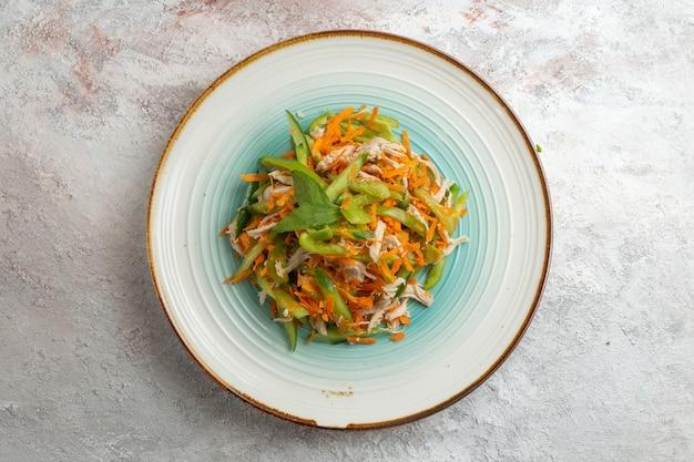 Вид сверху нарезанный овощной салат внутри тарелки на светлом белом фоне