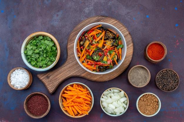暗い机の上に緑の調味料とプレート内の上面スライス野菜サラダ
