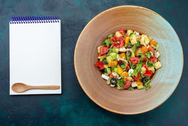 진한 파란색 책상에 메모장으로 접시 안에 고추를 뿌린 상위 뷰 슬라이스 야채 샐러드