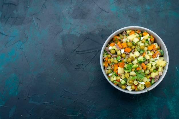 어두운 파란색 책상에 접시 안에 닭고기 조각으로 후추를 뿌린 상위 뷰 슬라이스 야채 샐러드
