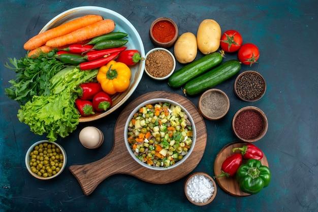 Вид сверху нарезанный овощной салат, приправленный кусочками курицы, внутри тарелки со свежими овощами на синем столе закуска обед салат овощная еда