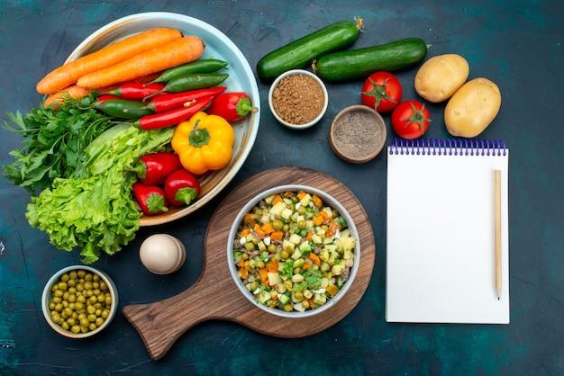 진한 파란색 책상에 신선한 야채와 함께 접시 안에 닭고기 조각으로 후추를 얹은 상위 뷰 슬라이스 야채 샐러드