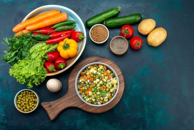 Вид сверху нарезанный овощной салат, приправленный кусочками курицы, внутри тарелки со свежими овощами на темно-синем столе