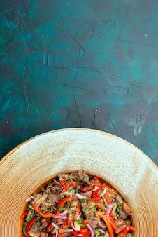Vista dall'alto di insalata di verdure a fette con carne riattaccata all'interno della piastra marrone su sfondo blu scuro insalata di cibo pasto foto di verdure