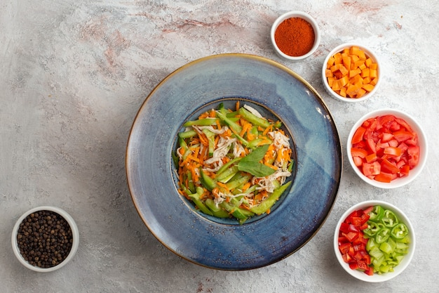上面図白い背景に調味料と他のスライス野菜とスライス野菜サラダ