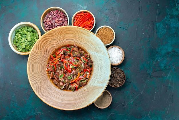 紺色の背景に調味料と一緒に肉とスライスした野菜の上面図食品食事サラダ野菜