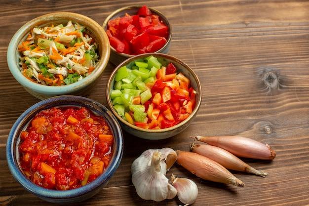 Вид сверху нарезанные овощи болгарский перец с помидорами на коричневом деревянном фоне овощная еда еда салат здоровье