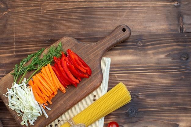 まな板の茶色の表面にスライスした野菜キャベツにんじんグリーンとコショウの上面図