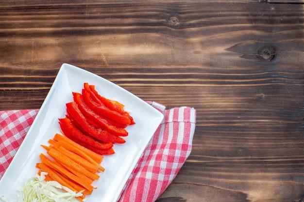 茶色の表面にスライスした野菜にんじんピーマンとキャベツの上面図