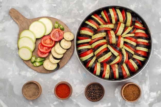 トマトとナスなどの新鮮な野菜をスライスし、明るい背景に熟した野菜食品の食事で調理した平面図