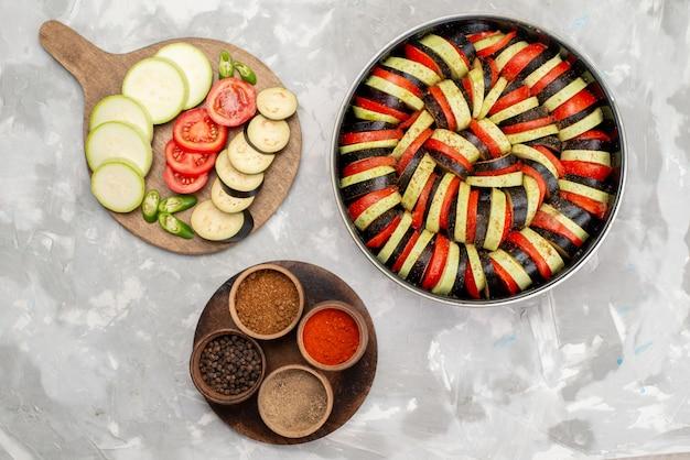 Вид сверху нарезанные овощи, такие как помидоры и баклажаны, свежие и приготовленные на светлом столе, еда из спелых свежих овощей