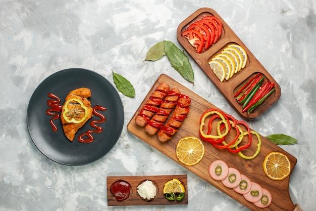 밝은 흰색 책상에 레몬과 토마토와 상위 뷰 슬라이스 야채