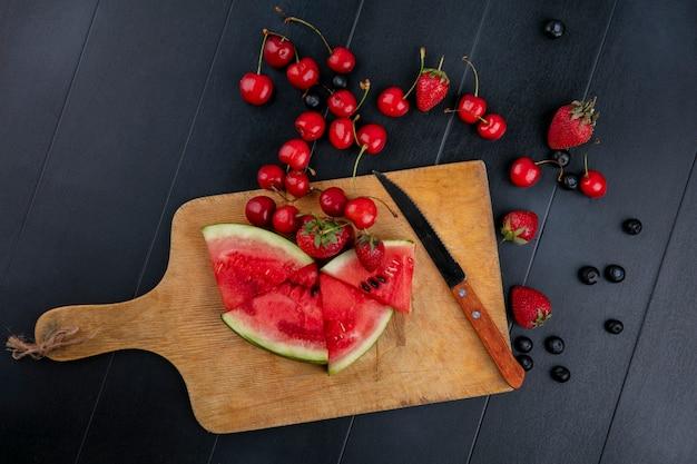 Вид сверху нарезанный арбуз на доске с клубникой и вишней с ножом на черном фоне
