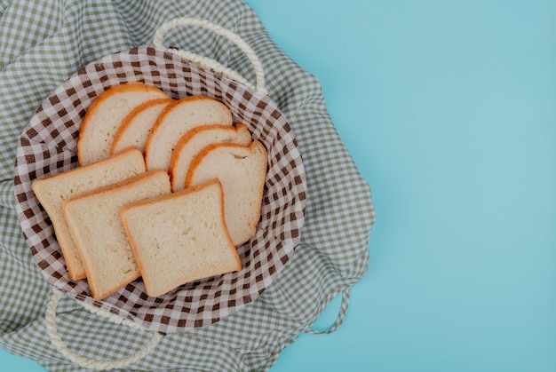 Top view of sliced white bread in basket on plaid cloth and blue background with copy space