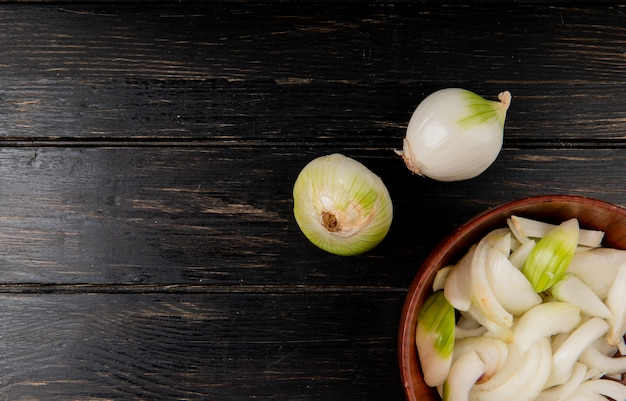 Top view of sliced white onion in bowl with whole ones on wooden surface with copy space