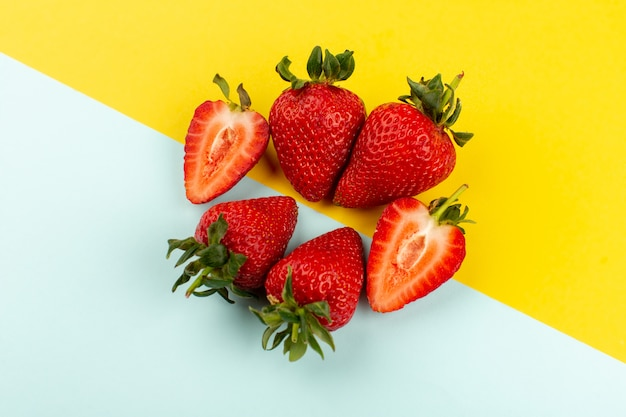 Top view sliced whole strawberries juicy mellow on the blue yellow floor