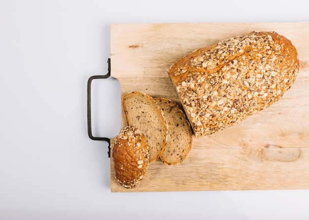 Top view of sliced wholegrain bread on chopping board over white background