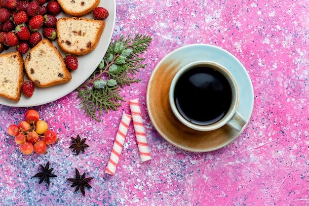 ピンクの机の上に新鮮な赤いイチゴとコーヒーのカップとスライスしたおいしいケーキの上面図