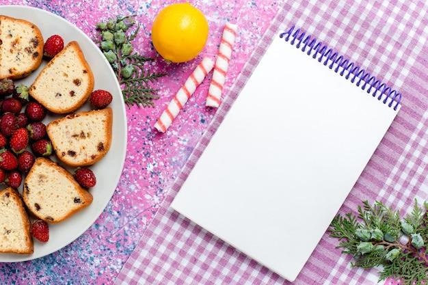 ピンクの机の上に新鮮な赤いイチゴとメモ帳でスライスしたおいしいケーキの上面図