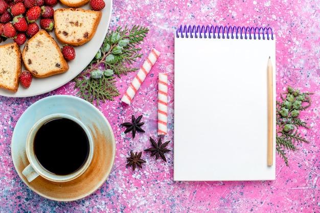 淡いピンクの机の上に新鮮な赤いイチゴのメモ帳とコーヒーのカップとスライスしたおいしいケーキの上面図