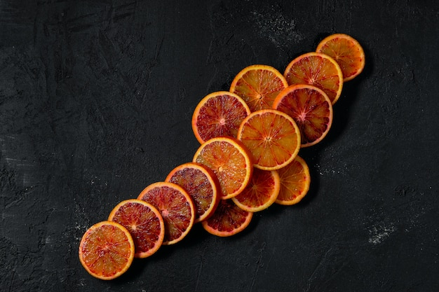 Top view of slices of blood orange on black abstract background
