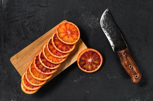 Top view of slices of blood orange on cutting board on black background