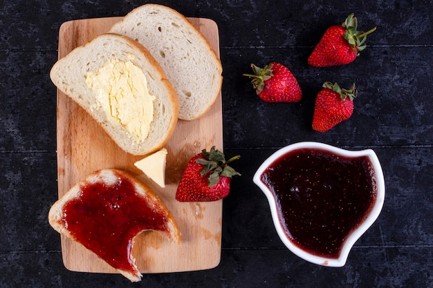 Top view slices of bread and butter with a slice of bread with jam on board with strawberries and jam in a saucer