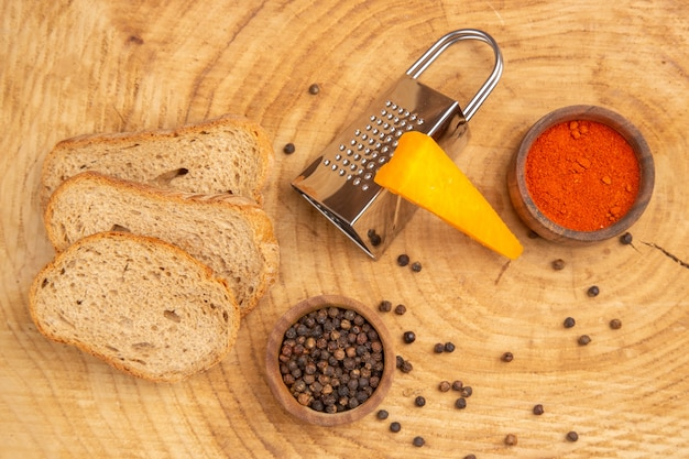 Top view slices of bread cheese grater different spices in small bowls on wooden table