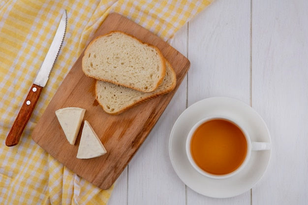 Top view of slices of bread with cheese on a blackboard with a knife on a yellow towel and a cup of tea on a white surface