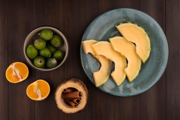 Vista dall'alto di fette di melone cantalupo su un piatto con feijoas su una ciotola con bastoncini di cannella con mandarini isolato su una parete in legno