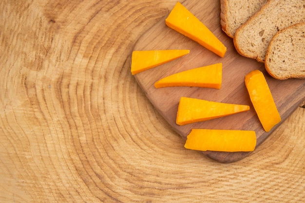 Top view slices of cheese slices of bread on cutting board on wooden table with copy space