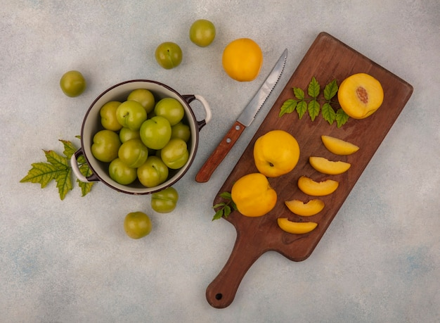 Top view of slices of fresh yellow peaches on a wooden kitchen board with knife with green cherry plums on a bowl on a white background