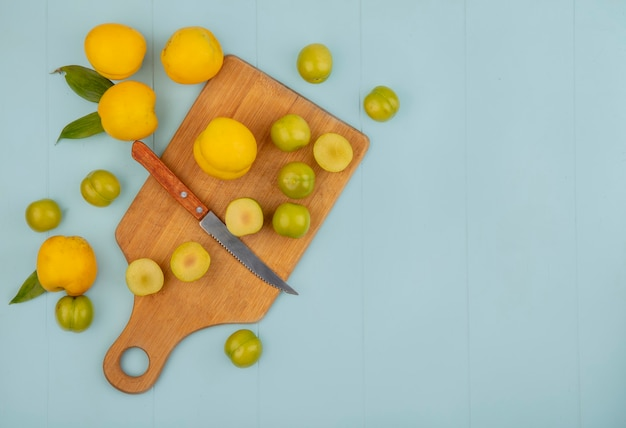 Top view of slices of green cherry plums on a wooden kitchen board with yellow peaches isolated on a blue background with copy space