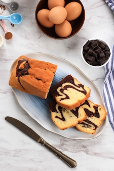 Top view slices of homemade marble cake on a white oval plate for accompanied tea time